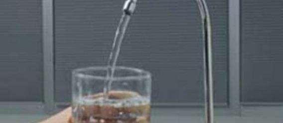 Llenando un vaso de agua de la llave a través de un filtro instalado en la misma tarja