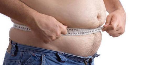 Hombre midiéndose el abdomen con cinta métrica