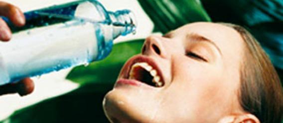 Mujer a punto de beber de una botella de agua