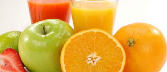 Frutas (naranjas, manzanas y fresa) y dos vasos con jugos de fruta