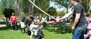 Niñas y niños juegan a saltar la cuerda, que impulsan adultos