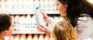 Madre con sus hijos leyendo el etiquetado de un producto en un pasillo del supermercado