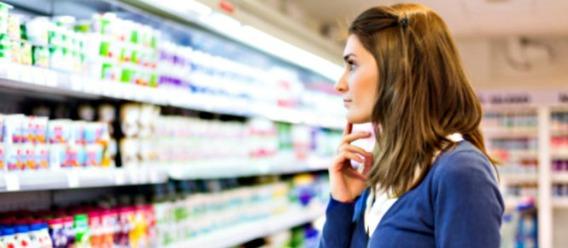 Mujer frente a un aparador de alimentos procesados pensando qué comprar
