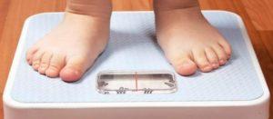 Imagen con los pies de un niño sobre una báscula para medir su peso corporal