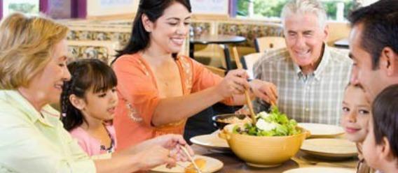 Niños y adultos comiendo juntos