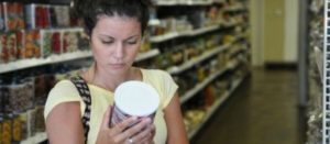 Consumidora revisando el etiquetado de un producto en el pasillo de un súper