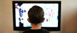 Niño de espaldas viendo televisión