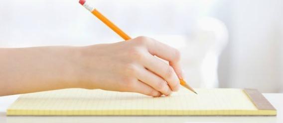 Persona escribiendo con un lápiz en un block
