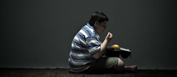 Niño obeso sentado en el piso comiendo con fondo gris