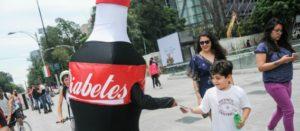 Botarga de refresco de Cola con la leyenda Diabetes entregando volantes informativos a personas que pasan por la calle
