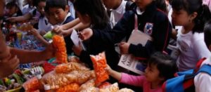 Niñas y niños comprando en un puesto afuera de la escuela