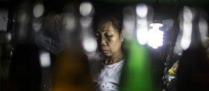 Rostro de una adulta mayor entre botellas de bebidas azucaradas