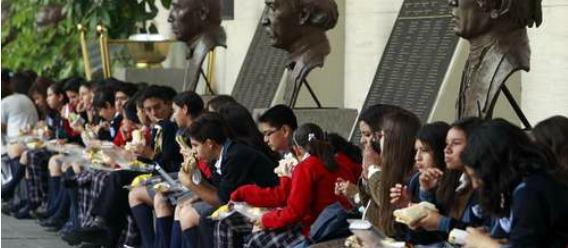 Estudiantes sentados comiendo durante el recreo