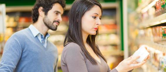 Consumidores revisando etiquetado de un producto en el súper