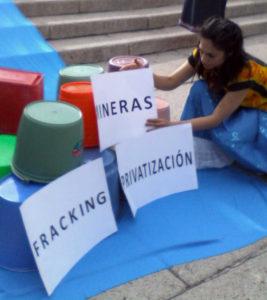 """Instalación al pie del Ángel de la Independencia con cubetas y las leyendas """"Fracking"""", """"Mineras"""" y """"Privatización"""""""
