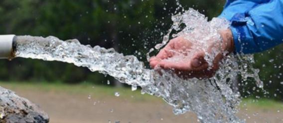 Manos juntas haciendo una cuenca frente al chorro de agua