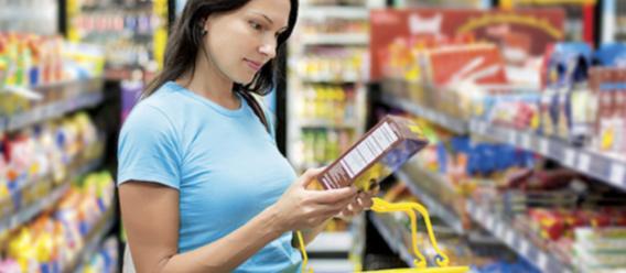 Chica en pasillo de supermercado intentando leer etiquetado nutrimental de una caja de cerales que tiene en las manos