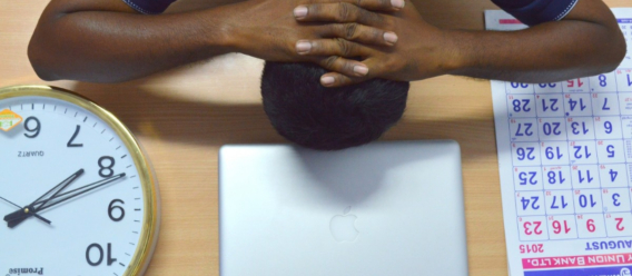 Foto de trabajador de oficina con cabeza sobre el escritorio con reloj grande y calendario