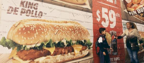 Publicidad de comida chatarra en la calle donde caminan un niño y su mamá
