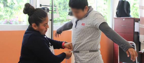 Maestra midiendo la cintura de un niño en escuela de Oaxaca, México