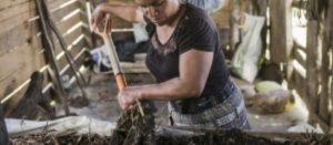 Agricultora familiar removiendo su tierra con una pala