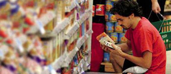 Chico en cuclillas leyendo el etiquetado de un producto en un pasillo del supermercado
