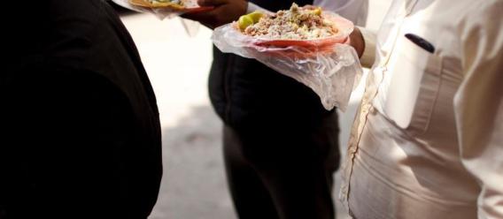 Imagen fragmentada de unos comensales con sobrepeso, solo se ven sus barrigas y los platos con tacos en sus manos