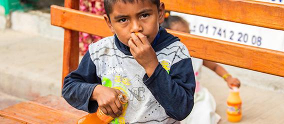 Niño sentado con una bebida azucarada en las manos