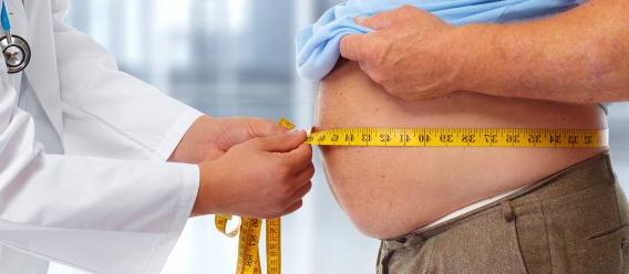 Médico midiendo la cintura de un paciente