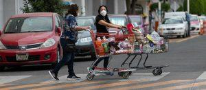 Consumidoras con tapabocas saliendo del súper con su compra de productos ultraprocesados