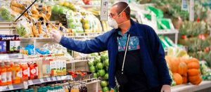 Hombre con tapabocas seleccionando verduras en en refrigerador de súper