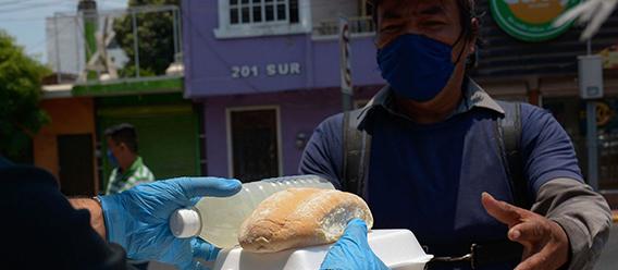 Una persona recibiendo un empaque con alimento acompañado de una botella de agua y un pan