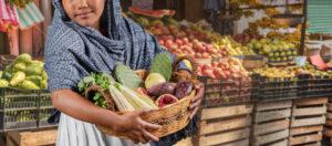 Mujer en mercado llevando el recaudo en su canasta
